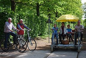 Eine Gruppe auf ihrer Draisine und zwei Fahrradfahrer treffen sich auf der Draisinenstrecke durch Westerstede