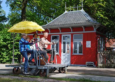 Das Draisinen Bahnwärterhaus in Westerstede mit einer von Gästen besetzte Draisine im Vordergrund