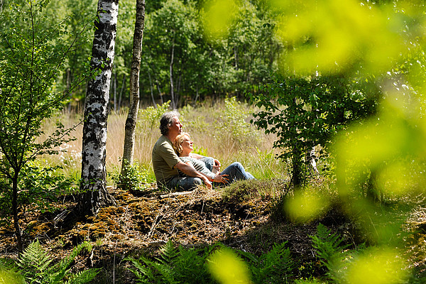 Paar sitzt Arm in Arm im Moor und blickt in die Weite