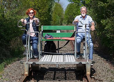 Ein Ehepaar fährt durch die Westersteder Landschaft mit einer Draisine
