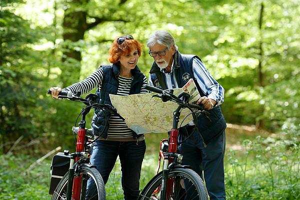 Paar mit E-Bikes im Wald schaut auf Ammerland Radkarte
