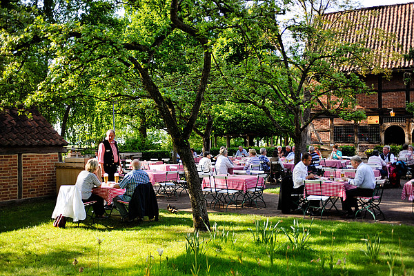 Blick in den Spieker Garten mit Tischen und vielen Menschen im Grünen Graß