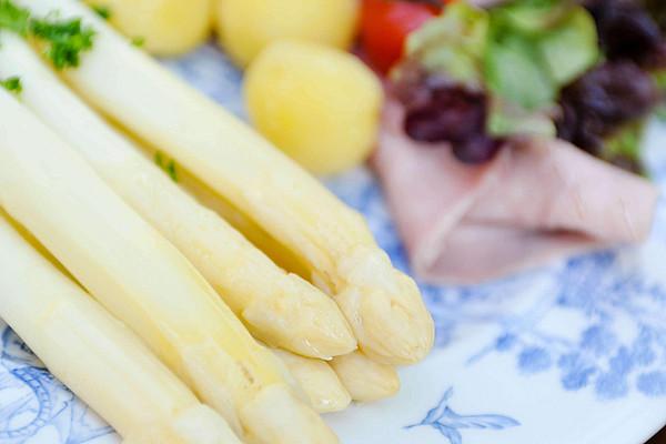 Spargel mit Kartoffeln und Speck angerichtet auf einem Teller